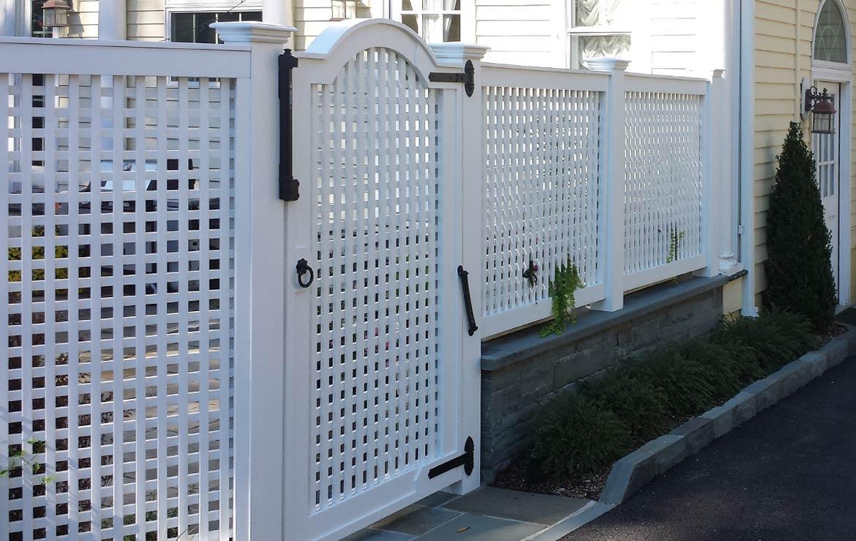 Custom lattice fence and gate. Bluestone curbing and wall.